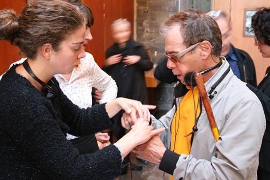Une personne de l'équipe Accès Culture explique le fonctionnement du boitier d'audiodescription à un spectateur aveugle en lui touchant les mains pour lui indiquer les manipulations à faire pour augmenter le volume sonore du casque.