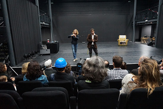 visite en LSF de la maison des Métallos. Le guide est sur scène accompagné d'une interprète LSF qui traduit son discours. Les spectateurs assis en salle, écoutent leur discours.