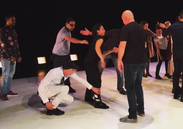 Les danseurs réalisent des mouvements sur la scène. Des personnes aveugles et malvoyantes les entourent et touchent les extrémités de leur mouvement pour se rendre compte de leurs gestes.