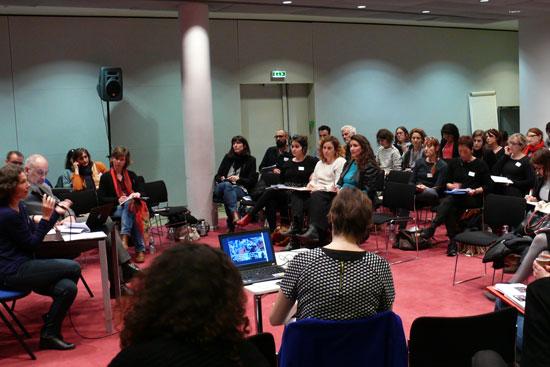 2 orateurs prennent la parole auprès d'une trentaine de personnes dans une salle configurée au format conférence